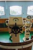 Steering wheel on the captain's bridge Stock Photos