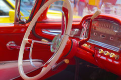 Steering Wheel Classic Car. Red interior dashboard and steering wheel of vintage classic car. Gear shift and the push and pull knobs are in imitation ivory. Car royalty free stock photo