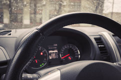 Steering wheel and control panel of modern car. Modern car interior fragment with steering wheel and control panel. Tonal correction photo filter effect, old Stock Photos