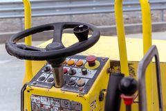 Steering wheel and control panel of road roller compactor or vibratory roller for tamping asphalt and soil stock images