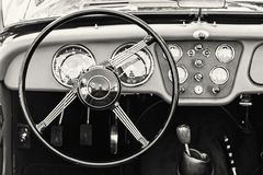 Steering wheel and dashboard in historic vintage car, black and Stock Image