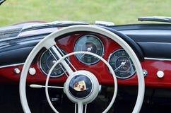 Steering wheel & dashboard of red vintage retro 1958 Porsche 356 Speedster sports motor car. The interior dashboard, dials, steering wheels and logo badge in Stock Photo