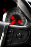 Steering Wheel comands and a dashboard as background Stock Photos