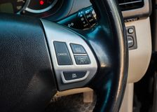 The steering wheel features cruise control buttons. Close up the steering wheel features cruise control buttons in car Royalty Free Stock Photos