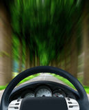 Steering wheel on forest highway Stock Photography