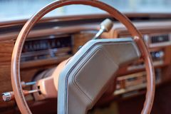 Steering wheel inside a vintage car. Close up detail of a brown steering wheel inside a vintage car with column controls and levers Stock Image