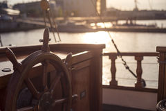 Steering wheel of an old wooden sailing ship in sunset Stock Photo