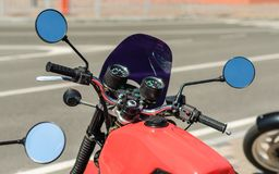Steering wheel of a red motorcycle cafe racer close up. Steering wheel of a red motorcycle cafe racer closeup royalty free stock image