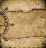 Steering wheel and torn vintage nautical map Royalty Free Stock Photos
