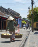 Steet seller in Hoi An in Vietnam. Rear view of street seller walking with baskets of fruit in Hoi An, Vietnam stock image