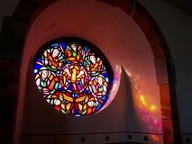 Stained glass rose window and sunlight reflections at Saint Michael`s Church in Steffeln, Rhineland-Palatinate, Germany. STEFFELN, GERMANY - MARCH 08, 2015 stock photography