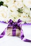 Steg blommor och gåvaasken med bandet på den ljusa tabellen Hälsning c Royaltyfri Bild
