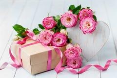 Steg blommor, trähjärta och gåvaasken på den blåa lantliga tabellen Härligt hälsningkort för födelsedag-, kvinna- eller moderdag royaltyfri bild