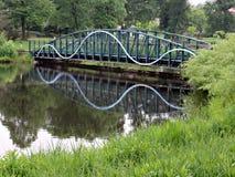 Steg, der im ruhigen Teich sich reflektiert Lizenzfreies Stockfoto