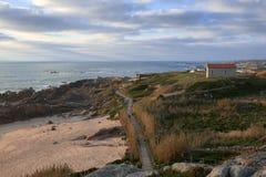 Steg trennt den Strand vom Hügel mit der Kirche an der Spitze lizenzfreie stockfotografie