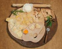 Stegade den hemlagad italiensk hjärta formade raviolit med ny ost, mjöl, ägget, valnötter och aromatiska örter på en lantlig rund Arkivbild