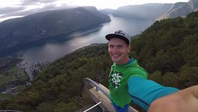 Stegastein viewpoint, Norway - July 22, 2018: Young traveller taking selfie on the top of view point with Beautiful. Fjord on background in Norway stock footage
