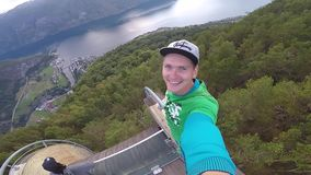 Stegastein viewpoint, Norway - July 22, 2018: Young traveller taking selfie on the top of view point with Beautiful. Fjord on background in Norway stock video footage