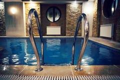 Stege för hastigt greppstänger i den blåa simbassängen royaltyfria bilder