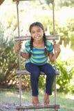 Stege för ung flickaklättringrep till treehousen royaltyfria bilder