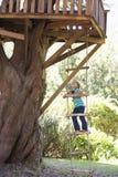 Stege för ung flickaklättringrep till treehousen arkivfoto