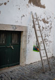 Stege med målarfärghinken mot den gamla väggen med den gröna dörren Arkivbilder