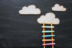 Stege som göras av färgrika chalks och blyertspennor bredvid moln över svart tavlabakgrund arkivbild