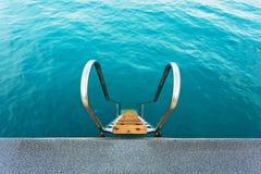 Stege som leder in i det uppfriskande kristallvattnet av ett hav arkivfoto
