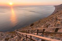 Stege som ner går till havet på en stenig klippa, solnedgång, Anapa, Ryssland royaltyfria bilder