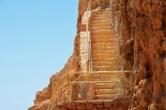 Stegen upp med metallledstänger vaggar på av den Masada fästningen i Israel arkivfoto