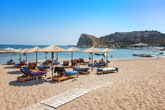 Stegna beach with sunshades and sunbeds, boats in background RH. ODES, GREECE Stock Image