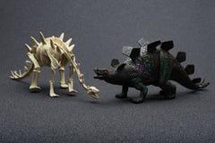 Stegosaurus toy and stegosaurus skeleton on dark background. Stegosaurus toy and stegosaurus skeleton on a dark background Royalty Free Stock Photo