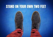 Stehen Sie auf Ihren eigenen zwei Fußnotentext und grauen Schuhen auf Füßen mit blauem Hintergrund Stockfotos