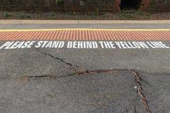 Stehen Sie bitte hinter der gelben Linie Unfallverhütungsvorschrift auf einer Zugplattform Lizenzfreie Stockbilder