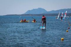 Stehen Sie oben Surfer-Mann Paddleboarding an Bord unter Kanus und Gewinn Stockbilder