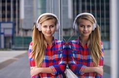 Stehende Außenseite der jungen Frau, die Musik auf Kopfhörern hört Lizenzfreie Stockfotografie