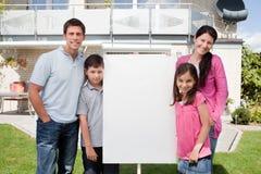 Stehende Außenseite der kleinen Familie mit einem leeren Zeichen Lizenzfreie Stockbilder