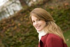 Stehende Außenseite der reifen Frau, die einen roten Mantel trägt lizenzfreies stockbild
