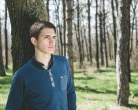 Stehende Außenseite des jungen Mannes im Wald Stockbild