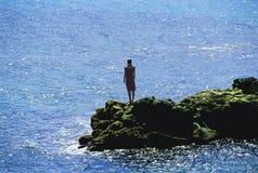 Stehende Felsen der jungen Frau, heraus schauend zum Meer Lizenzfreie Stockfotografie