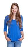 Stehende Frau in einem blauen Hemd lachend über Kamera Stockfoto