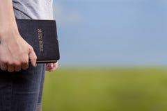 Stehende Holding die Bibel auf einem Gebiet Stockbilder