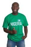 Stehender Sportfan von Nigeria, das Daumen zeigt lizenzfreies stockfoto