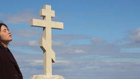 Stehendes allein nahes Kreuz der traurigen Frau nach Begräbnis, Schmerz auf dem Gesicht, betend zum Gott stock video
