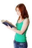 Stehendes jugendlich Mädchen, das ein Buch liest. Lizenzfreies Stockfoto