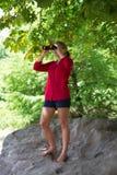 Stehendes Mädchen 20s mit Ferngläsern, ihre Umwelt beobachtend Lizenzfreie Stockfotografie
