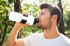 Stehendes und Trinkwasser des attraktiven jungen Sportlers draußen lizenzfreies stockfoto