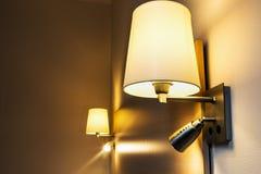 Stehlampe auf der Wand über dem Bett im Raum Lizenzfreie Stockfotografie