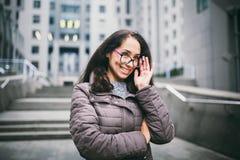 Steht schöner junger Brunette Geschäftsfrau des Porträts in der Jacke und in der Strickjacke auf Hintergrundbürogebäude, Geschäft lizenzfreies stockbild