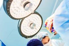 Steht weibliche Chirurgen unter einem Raum der chirurgischen Lampe in Kraft bei der Ausführung einer Operation auf einem blauen H stockfoto